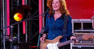 "Hear Bonnie Raitt Transform INXS' ""Need You Tonight"" Into A Gritty, Smoldering Blues Tune"
