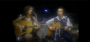 1976: Paul Simon & George Harrison Perform 'Homeward Bound' In SNL